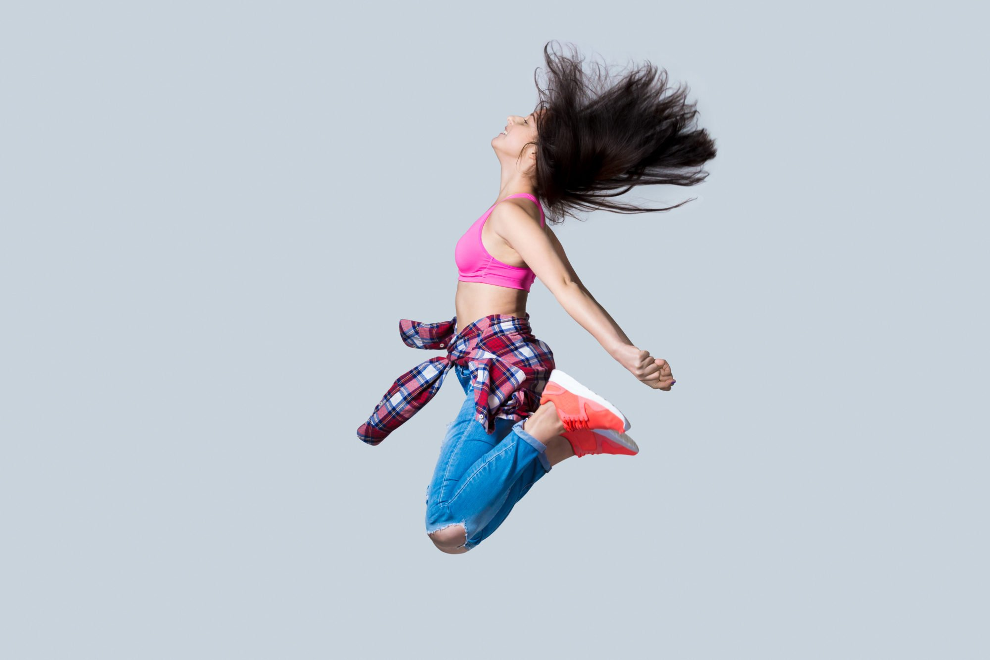 Beautiful young happy smiling fit modern hip-hop dancer woman working out wearing jeans, jumping, studio, gray background, full length